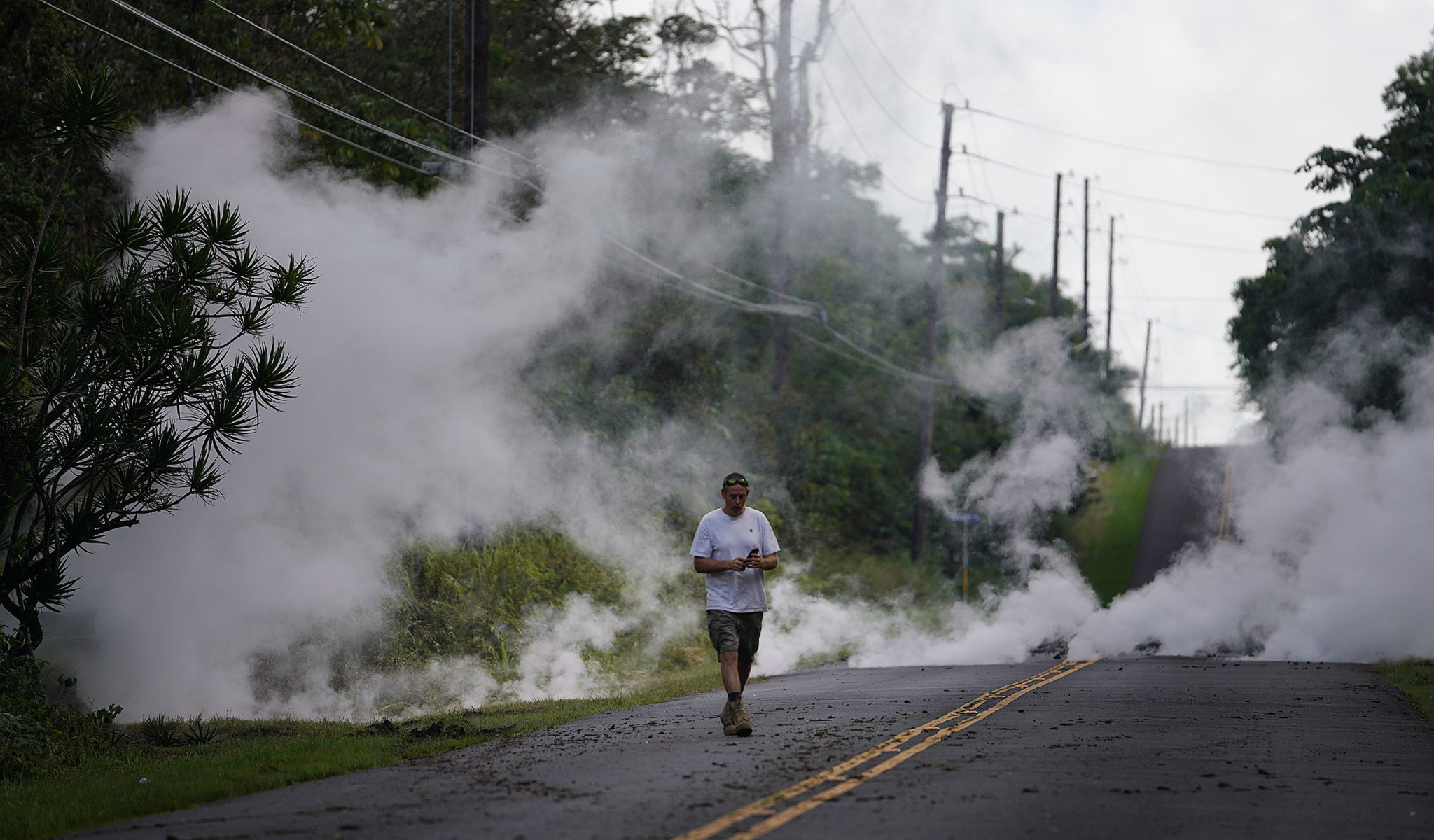 Roads inside Leilani Estate with smoke from cracked fissures as molten lava flows under heating up the surface in Pahoa, Hawaii.