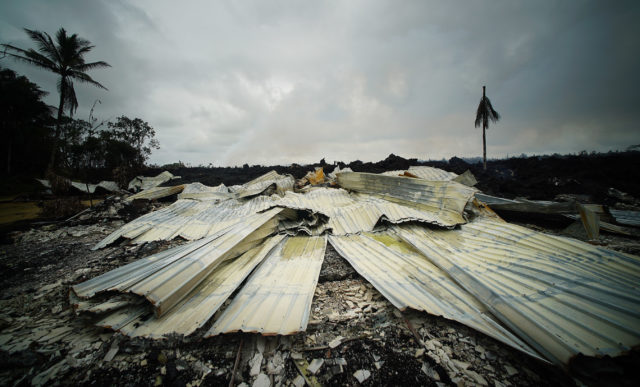 Aluminum roofing material lays on the foundation of a home that was engulfed by lava along Leilani Avenue. Puna, Hawaii.