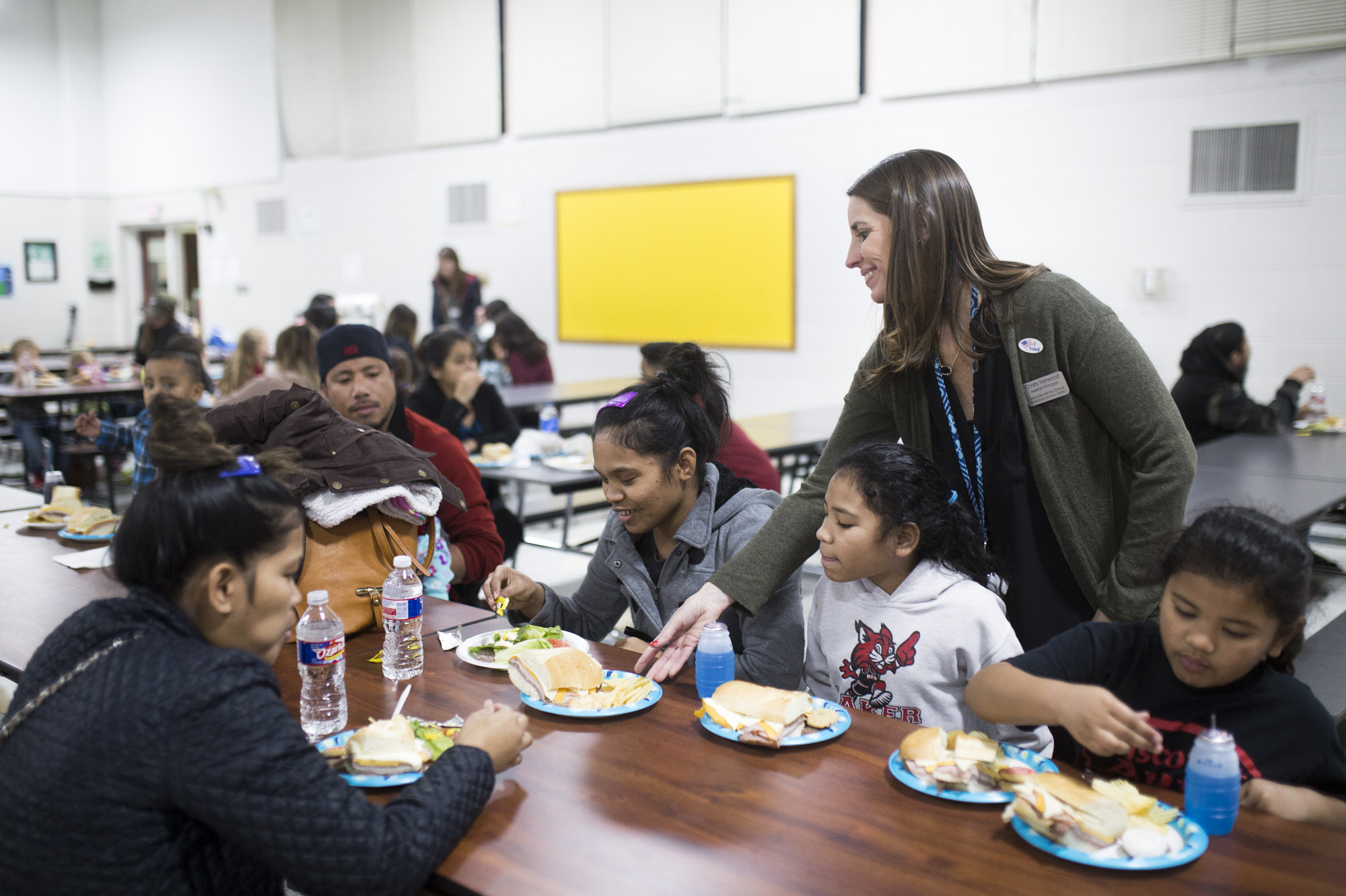 Assitant Principal of Jones Elementary School Christy Norwood (right) gives a plate of food to Tien Lalimo (center) at the Coke with a Cop event at Jones Elementary School in Springdale, February 13, 2018.
