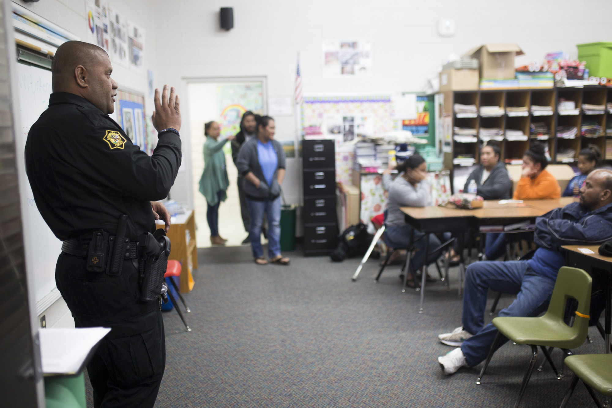 Robert Aini, school resource officer, (left) speaks with Marshallese parents at the Coke with a Cop event at Jones Elementary School in Springdale, February 13, 2018.