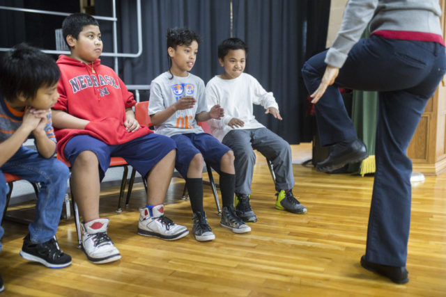 ESL Instructional Facilitator Deanna Self (right) demonstrates a stomp dance as Marshallese students (from left) Johnny Zachrias 9, Arbi Peter 10, Elijah Pound 9 and Jonathan Morelik 9 watch at Robert E. Lee Elementary School in Springdale, February 14, 2018.