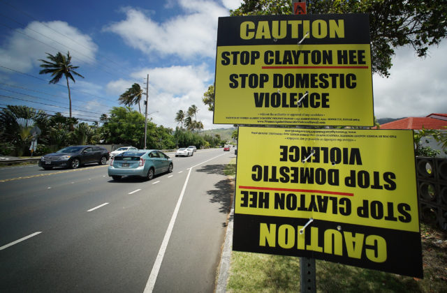 Caution Stop Clayton Hee Stop Domestic Violence signs along Kalanianiole Highway.