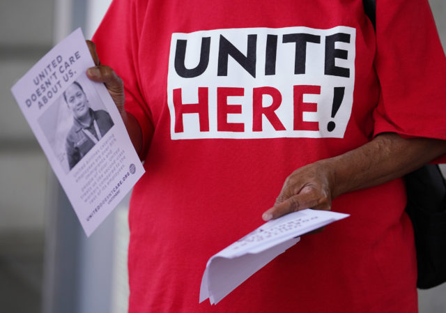 Imaculata Afituk hands out leaflets asking the public for support for United Airlines food workers to unionize at Daniel Inouye International Airport, United curbside area.