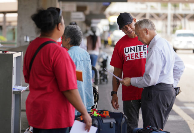 Victor Gonzalez hands out leaflets asking the public for support for United Airlines food workers to unionize at Daniel Inouye International Airport, United curbside area.