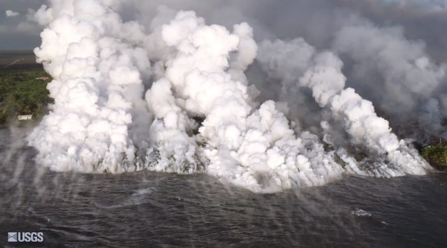 This image taken from video on Monday, June 4, 2018 and provided by the U.S. Geological Survey shows lava from a fissure flowing into the ocean at Kapoho Bay at the town of Kapoho on the island of Hawaii. See the structure at lower left for scale. The flow front was about a half-mile wide, with lava building a delta a few hundred yards into the bay. Hundreds of homes were destroyed overnight. (U.S. Geological Survey via AP)