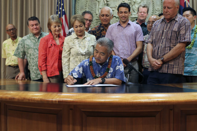 Hawaii Gov. David Ige, with state lawmakers standing behind him, signs legislation in Honolulu on Wednesday, June 13, 2018 that bans a pesticide scientists have found could hinder the development of children's brains. Ige and state lawmakers say Hawaii is the first state to ban chlorpyrifos. (AP Photo/Audrey McAvoy)
