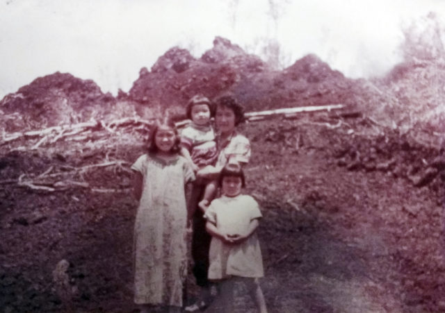 This 1955 photo provided by Rosemary Kawamoto shows her, at 9, left, her mother Mildred Nii holding her sister Carol, 3, with her sister Ethel Jane, 5, right, posing in front of a still-smoking cinder cone after an eruption on their family farm at Pahoa on the island of Hawaii. Lava spared their house, but her family never moved back because her mother, a city girl from Honolulu, objected. The family moved to Hilo, the largest town on the Big Island, and sold the farm. (Courtesy Rosemary Kawamoto via AP)