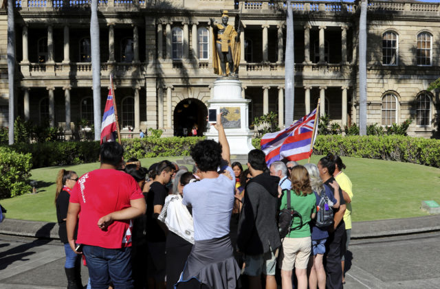 Opponents of a giant telescope planned for Hawaii's Mauna Kea pray in front of a statue of King Kamehameha outside the Hawaii Supreme Court building on Thursday, June 21, 2018. The court is considering an appeal of a decision to grant the project a construction permit. Opponents say it will desecrate land that's sacred to Native Hawaiians. (AP Photo/Jennifer Sinco Kelleher)