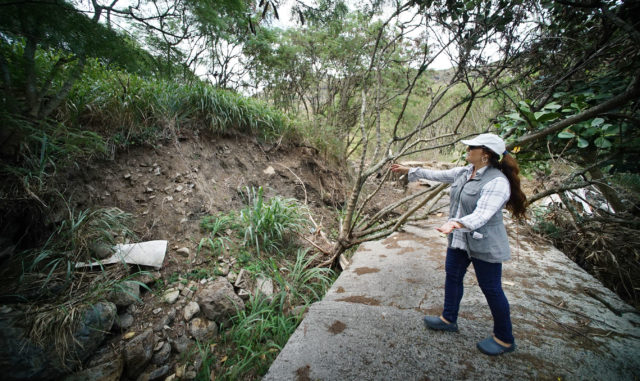 Elizabeth Reilly President of Livable Hawaii Kai points to erosion from the April 2018 storm that damaged the valley at 965 Kamilonui Place.