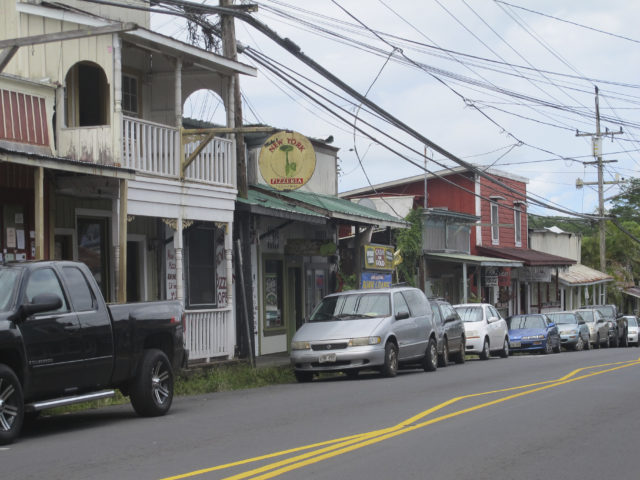 FILE - This Sept. 8, 2014 file photo shows downtown Pahoa, Hawaii. The small, rural town of Pahoa is the gateway to the eruption pouring rivers of lava out of Hawaii's Kilauea volcano. Historic wooden buildings lining its main street are just a few miles from where a cinder cone shooting lava into the sky has popped up in people's yards. Tourism to parts of the island has plummeted since the volcano began erupting in a residential neighborhood and burning down homes in May. (AP Photo/Audrey McAvoy, File)