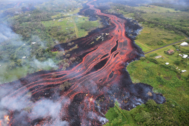 FILE - In this May 19, 2018, file photo released by the U.S. Geological Survey, lava flows from fissures near Pahoa, Hawaii. The small, rural town of Pahoa serves as a gateway to Hawaii Volcanoes National Park, which is normally the state's most popular tourist destination but has closed indefinitely because of dangers to staff and visitors. (U.S. Geological Survey via AP, File)