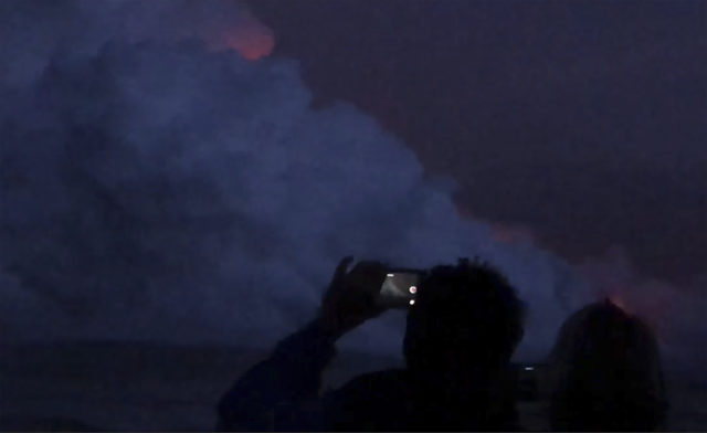 In this July 16, 2018, image taken from video provided by Will Bryan, tourists watch as lava from Hawaii's Kilauea volcano enters the ocean near Kapoho, Hawaii. Bryan, a paramedic who was on vacation in Hawaii when the accident happened, says both he and his girlfriend, Erin Walsh, suffered burns and cuts from the volcanic debris. (Will Bryan via AP)