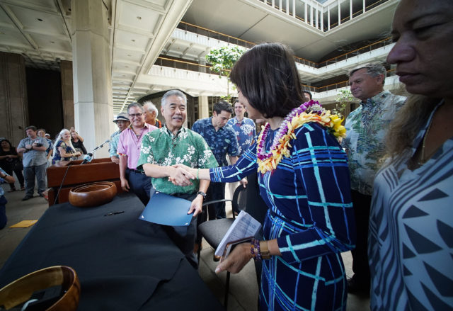 Governor David Ige shakes Sen Kim's hand after signing the SB2571 oxybenzone ban at the Capitol Rotunda.