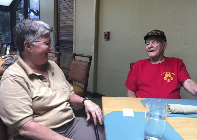 In this Monday, Aug. 13, 2018, photo Daniel Crowley, right, a 96-year-old U.S. Army Air Corps veteran from World War II who was held by Japan as a prisoner of war in the Philippines and Japan, speaks with his wife, Kelley Crowley, during an interview in Honolulu. (AP Photo/Audrey McAvoy)