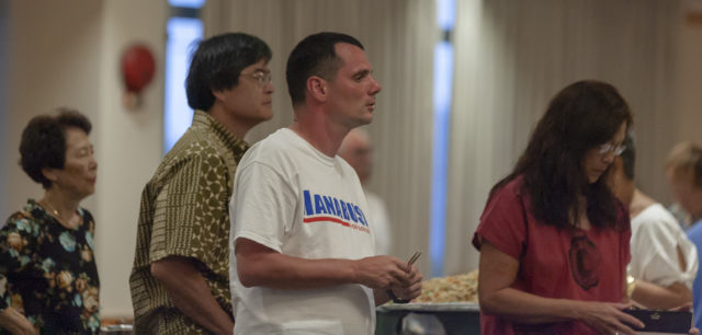 Joseph Mangi, center, of Waikiki , supporter of Hawaii Democratic Gubernatorial candidate Colleen Hanabusa looks on as the results of the first printout is announced by the local news at Hanabusa's election night headquarters in the Japanese Cultural Center, Saturday, Aug. 11, 2018, in Honolulu.