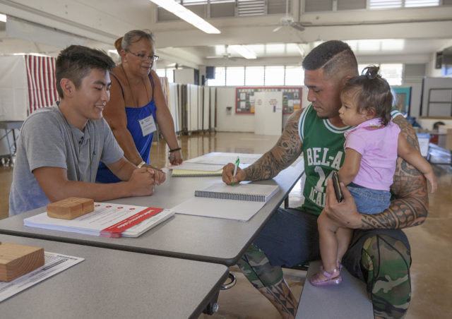 Voter precinct volunteers Tyler Maruno, left, and Letitia Corpuz, center, help Matt Coleman, right, holding his daughter Natalee, sign-in before voting at Lanakila Elementary School, Saturday, Aug. 11, 2018, in Honolulu.